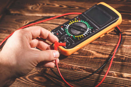 Multimeter and two test leads on a wooden background. A man's hand holds two test leads. A studio photo with hard lighting. Standard-Bild