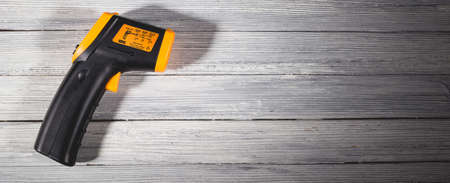 Yellow-black pyrometer on a wooden background. A device for non-contact temperature measurement. Studio photo.