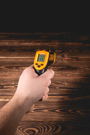 A man holds a yellow-black pyrometer on a wooden background. A device for non-contact temperature measurement. Studio photo.