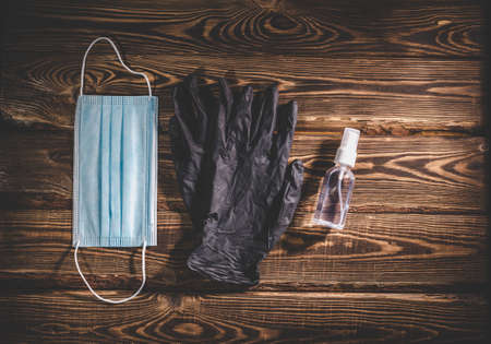 Medical mask, black rubber gloves and a transparent sanitizer on a wooden background.  virus protection medical concept. Studio photo with vignetting. Standard-Bild