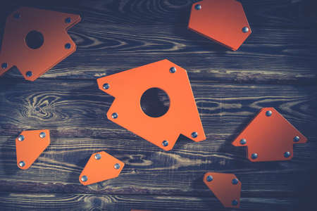 A set of orange magnetic corners for welding metal structures with a fixed angle value. Studio photo with hard lighting on a wooden background. Standard-Bild