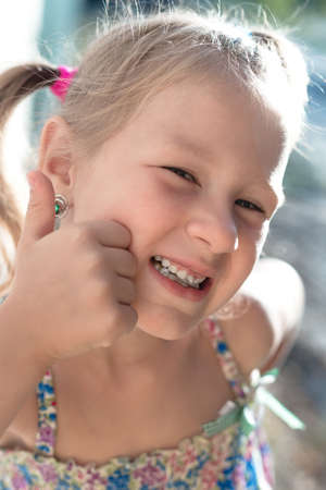 Portrait of a little girl with a wobbly baby tooth and a thumb up.