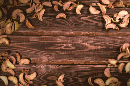 Slices of dried apples on a wooden background. A studio photo with hard lighting. Standard-Bild