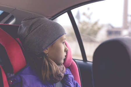 Little girl sit in the car seat and looks out the window.