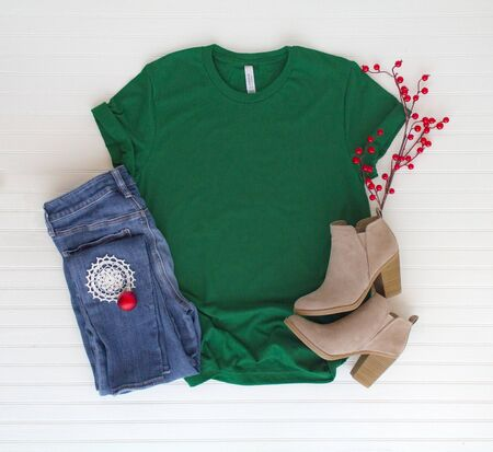 Green shirt top view and styled with Christmas items with white background
