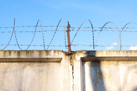 barb wire: Wall with barbed wire on a background of blue sky