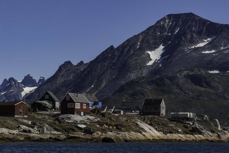 Colorful houses of the fishing town in Greenland. Mountains in the background.