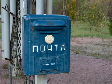 Old mailbox in memorial complex in Chernobyl Exclusion Zone. Text on the box: post and taking out at 12:00. Chernobyl, Ukraine