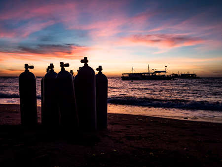 Sunrise over the beach in Philippines. Diving boats waiting for early morning divers. Silhouette of diving tanks in the foreground.