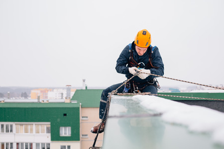 Industrial climber in uniform and helmet sitting on the roof preparing to the work in winter