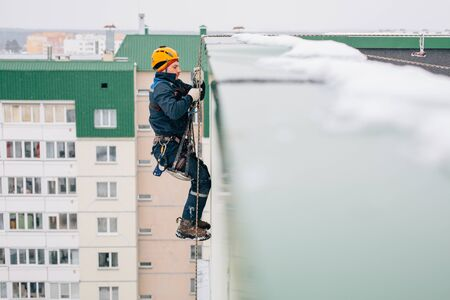 Industrial climber in uniform and helmet getting down from the snowy roof in winter Stock Photo