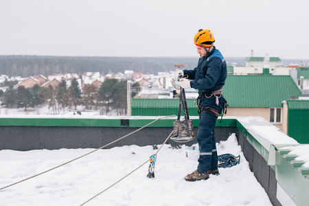 Industrial climber in uniform and helmet preparing to the work on the roof in winter