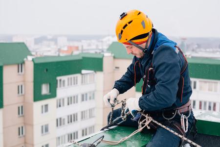 Escalador industrial en uniforme y casco sentado en el techo preparándose para el trabajo en invierno
