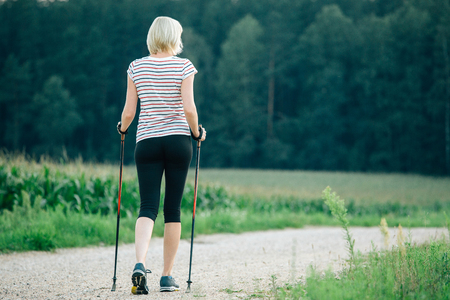 Nordic walking - active woman exercising outdoor. Back view of blonde girl workout near the forest. Adventure and exercising concept