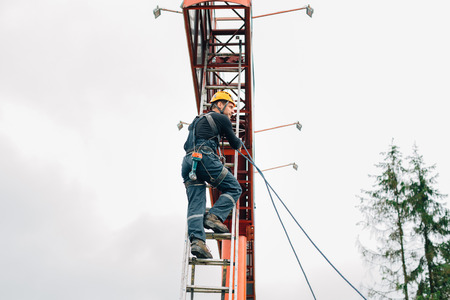Industrial climber climbing stairs to the billboard