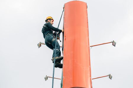 Industrial climber hangs a poster on a billboard