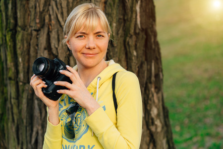 Girl with professional camera in hands. Close up of female photographer in park. Stock Photo