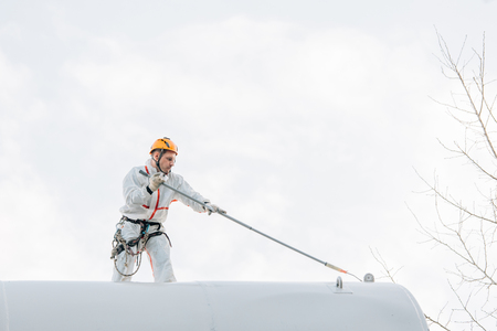 Industrial climber in helmet and uniform painting water tower. Professional Painter working on height. Risky job. Extreme occupation.
