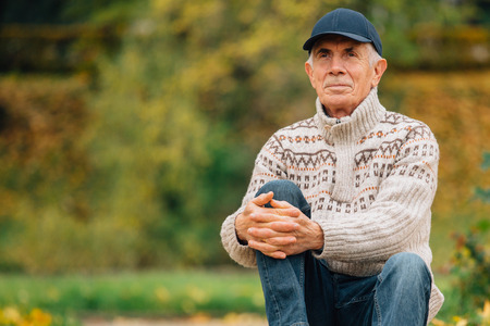 Portrait of pretty senior man in cap sitting in colorful autumn park. Pensioner resting outdoors. Beutiful fall.