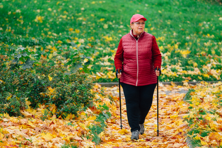 Senior woman standing with nordic walking poles in colorful autumn park. Healthy life concept. Mature woman resting after exercise outdoors.