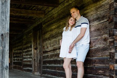 Young pretty couple in love standing on veranda of old house. Handsome blonde girl hugging her boyfriend Stock fotó