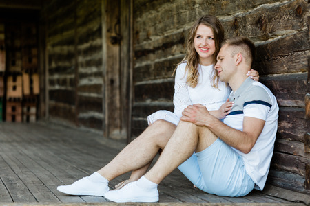 Young pretty couple in love sitting on veranda of old house. Handsome blonde girl in white dress hugging her boyfriend Standard-Bild