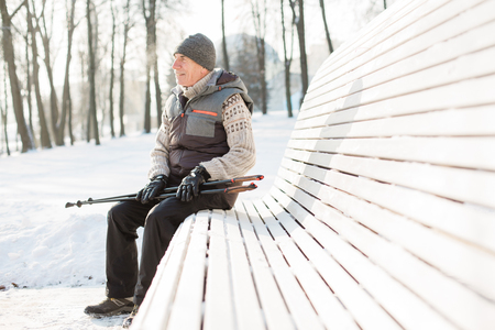 Senior man sitting with nordic walking poles in winter  park. Healthy lifestyle concept. Mature man resting after exercise outdoors. 版權商用圖片