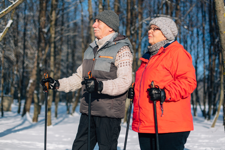 Pretty senior couple standing with nordic walking poles in winter park. Mature woman and old man resting outdoors. Healthy lifestyle concept.