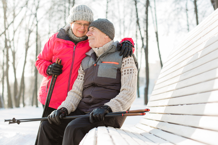 Pretty senior couple sitting with nordic walking poles in winter park. Mature woman and old man resting outdoors. Healthy lifestyle concept.