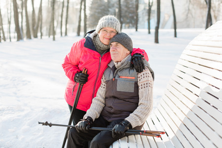 Pretty senior couple sitting with nordic walking poles in winter park. Mature woman and old man resting outdoors. Healthy lifestyle concept. Reklamní fotografie