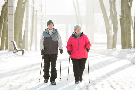 Senior couple walking with nordic walking poles in winter park. Mature woman and old man doing exercise outdoors. Healthy lifestyle concept. Zdjęcie Seryjne