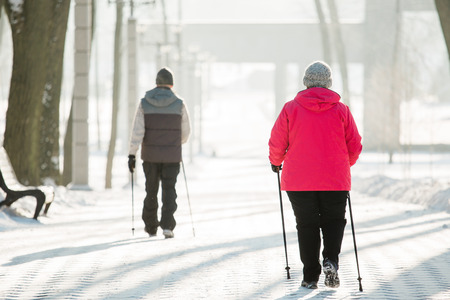 Senior couple walking with nordic walking poles in winter park. Mature woman and old man doing exercise outdoors. Healthy lifestyle concept. Foto de archivo