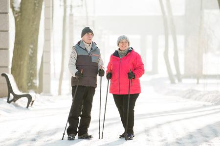 Las parejas ancianas caminando con bastones de marcha nórdica en Winter Park. Mujer madura y anciano haciendo ejercicio al aire libre. Concepto de estilo de vida saludable.