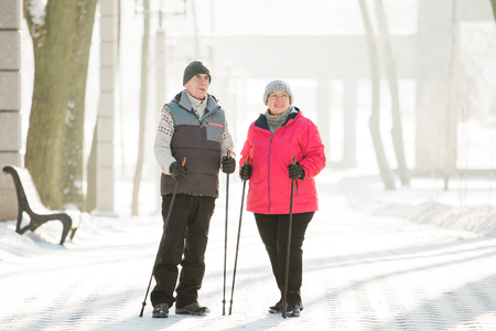 Senior couple walking with nordic walking poles in winter park. Mature woman and old man doing exercise outdoors. Healthy lifestyle concept. 스톡 콘텐츠