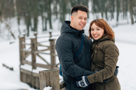 Winter portrait of young beautiful happy smiling couple outdoors. Christmas and winter holidays. Man and woman in snowy park