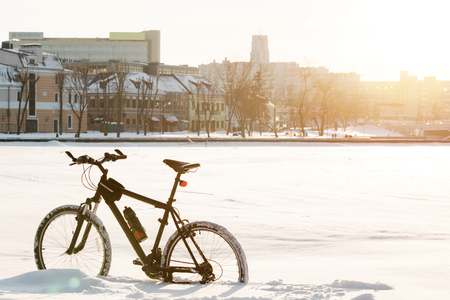 Winter season cycling. Black bicycle on the snow inte city center. Sport at any time of year concept. 版權商用圖片