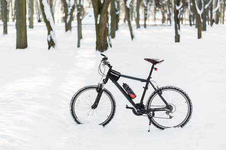 Winter season cycling. Black bicycle on the snow. Sport at any time of year concept.