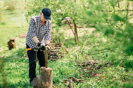 Senior man in baseball cap with axe chopping wood. Elderly arborist man working in garden. Active retirement lifestyle concept.