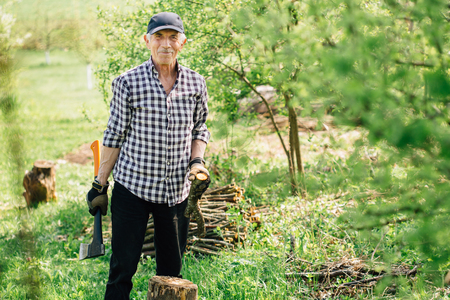 Senior man in baseball cap with axe chopping wood. Elderly arborist man working in garden. Active retirement lifestyle concept.