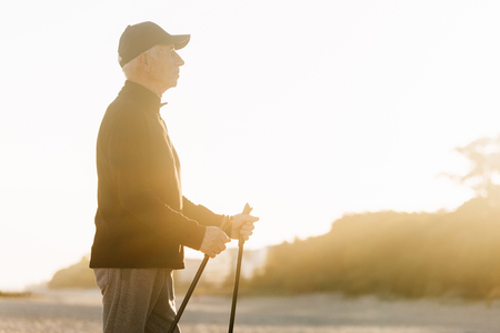Nordic walking - senior man working out on beach. Healthy lifestyle