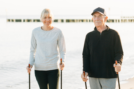 Nordic walking - senior man and pretty young girl working out on beach. Healthy lifestyle. Candid photo of father and daughter. 版權商用圖片