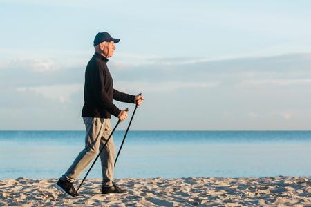 Nordic Walking - älterer Mann, der am Strand trainiert. Gesunder Lebensstil
