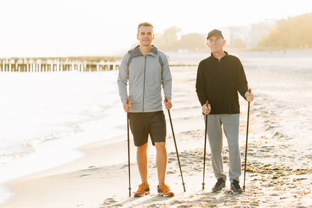 Nordic walking - senior man and young man working out on beach. Healthy lifestyle. Candid photo of father and son resting together on vacation