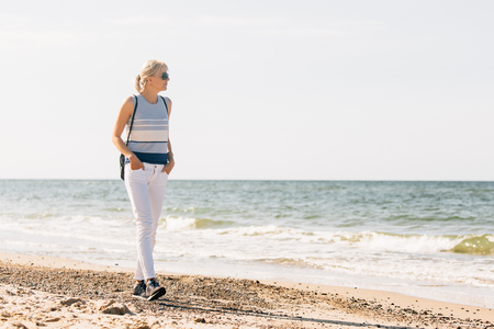 Young, beautiful blonde girl walking at the beach. Stylish woman in white pants and sunglasses near sea 版權商用圖片