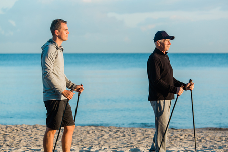 Nordic walking - senior man and young man working out on beach. Healthy lifestyle. Father and son resting together on vacation 版權商用圖片