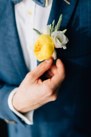 Groom in a blue suit with colorful yellow boutonniere. Wedding day man getting ready.