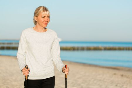 Pretty young woman resting after nordic walking on the beach. Healthy sport life concept Reklamní fotografie