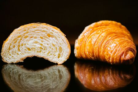 cut sliced croissant isolated on black glass. Delicious fresh pastries