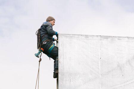 Industrial climber repair billboard. Risky job. Work on height. Metal construction. Electric screwdrive.