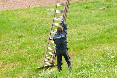 Construction worker carrying a ladder. Industrial climber getting ready for work. Risky job